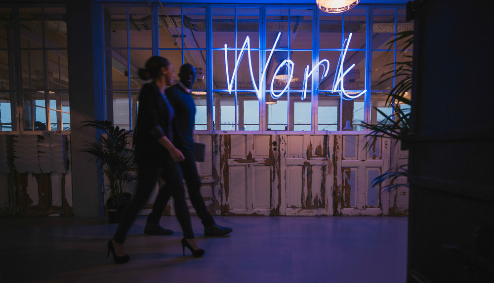 Business executive walking through office corridor with neon light work sign.