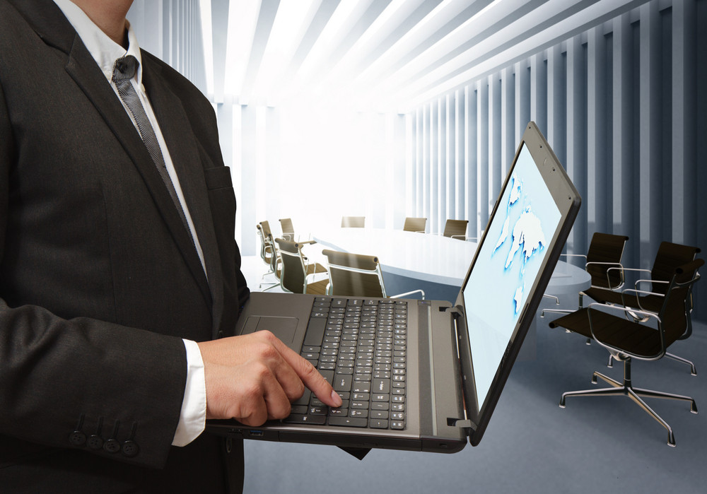 Business Man Using Laptop Computer In Board Room