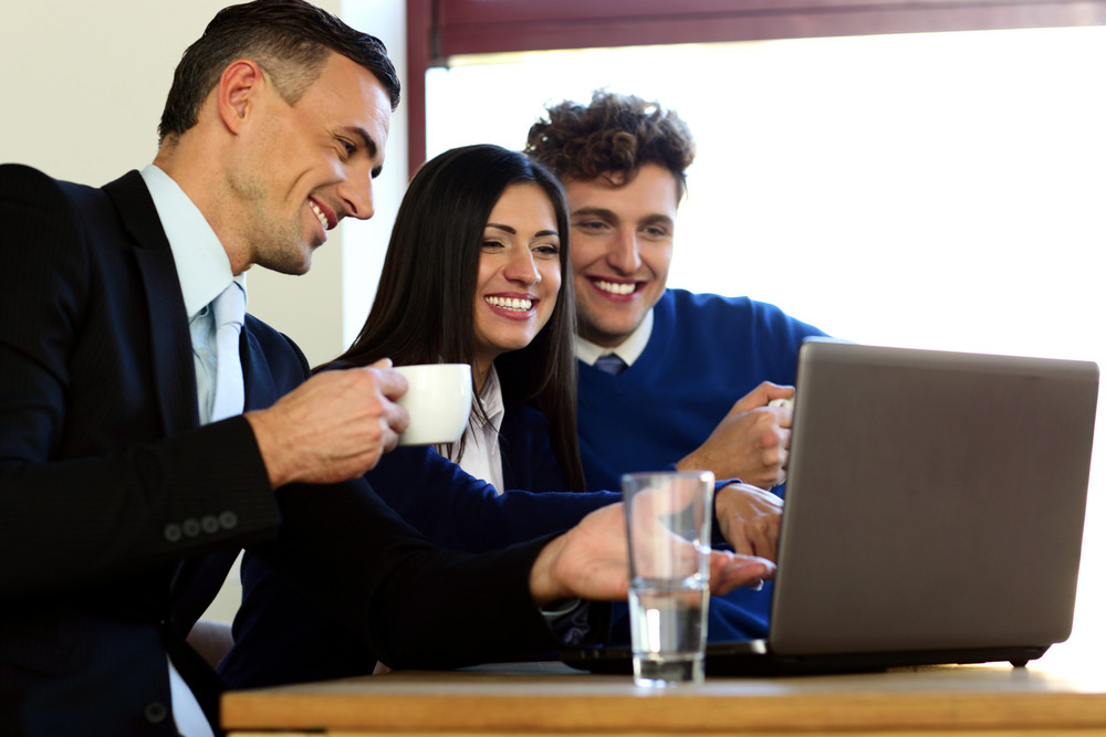 Business people using laptop together in office