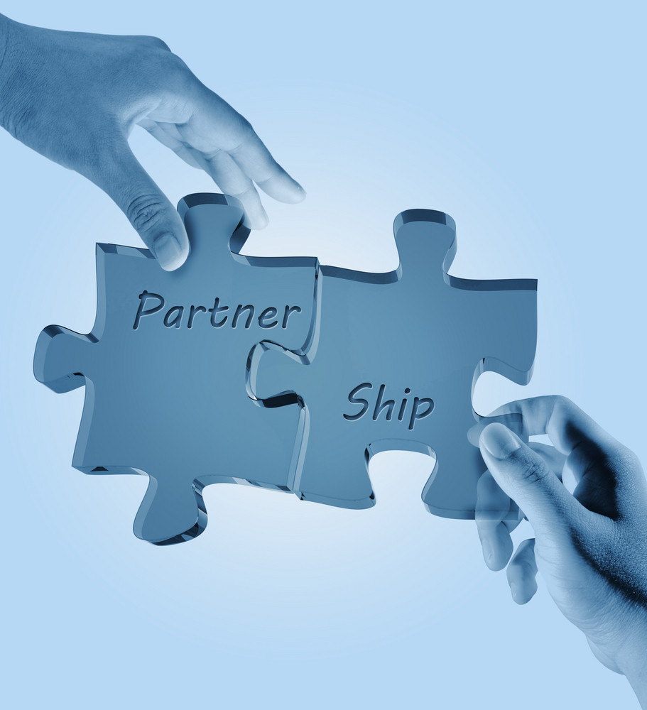 """Businessman And Woman Hold """"partnership"""" Written Puzzle Pieces"""