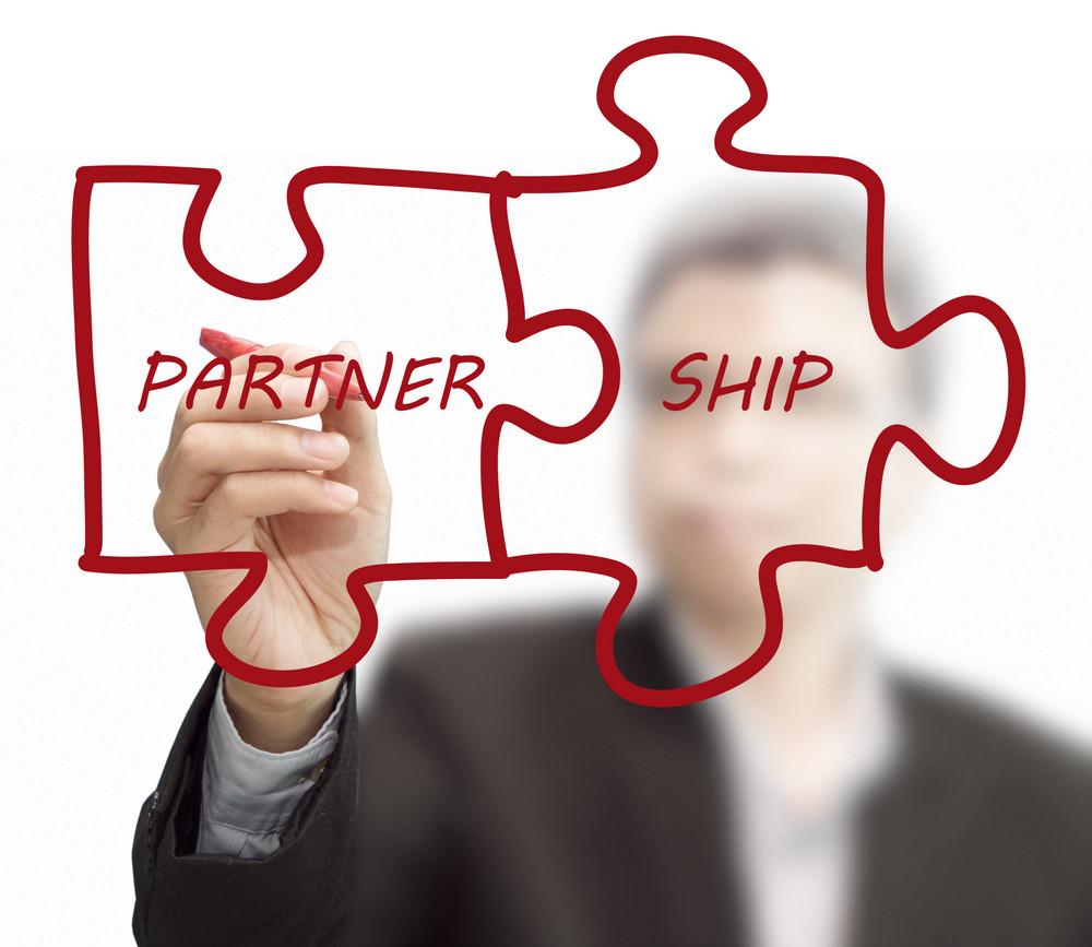 "Businessman Drawing ""partnership"" Written Puzzle Pieces"