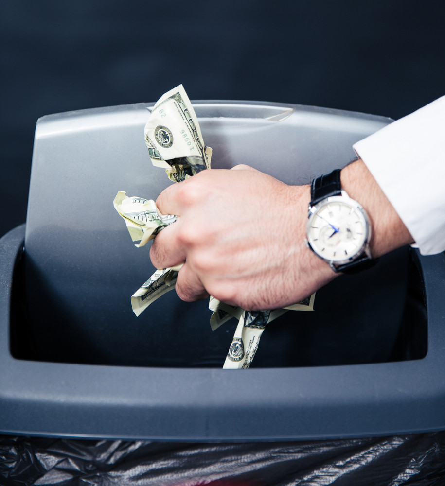 Businessman hands throwing US dollar bills in trash bin