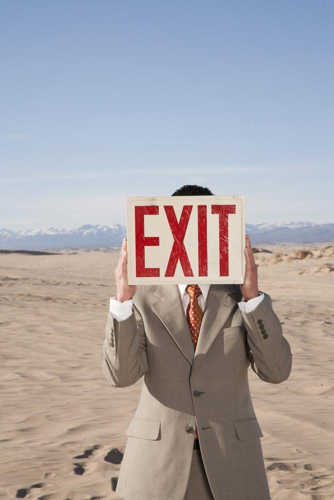 Businessman holding exit sign