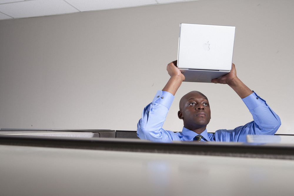 Businessman holding laptop over head in office