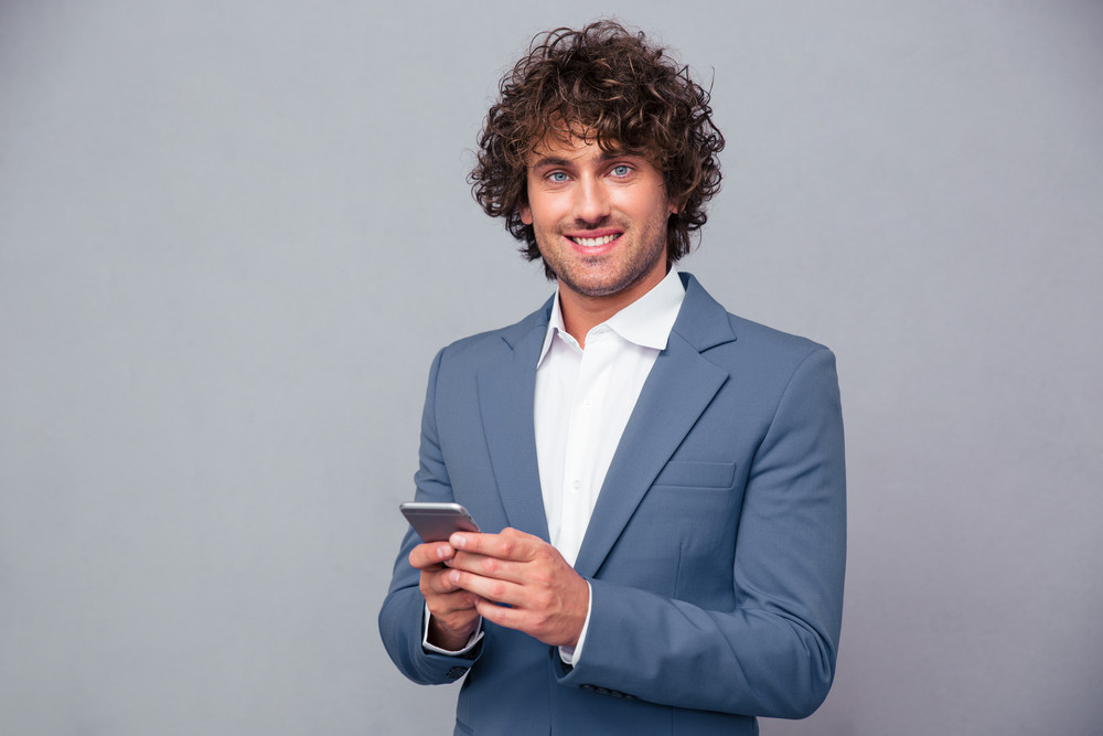 Businessman holding smartphone and looking at camera