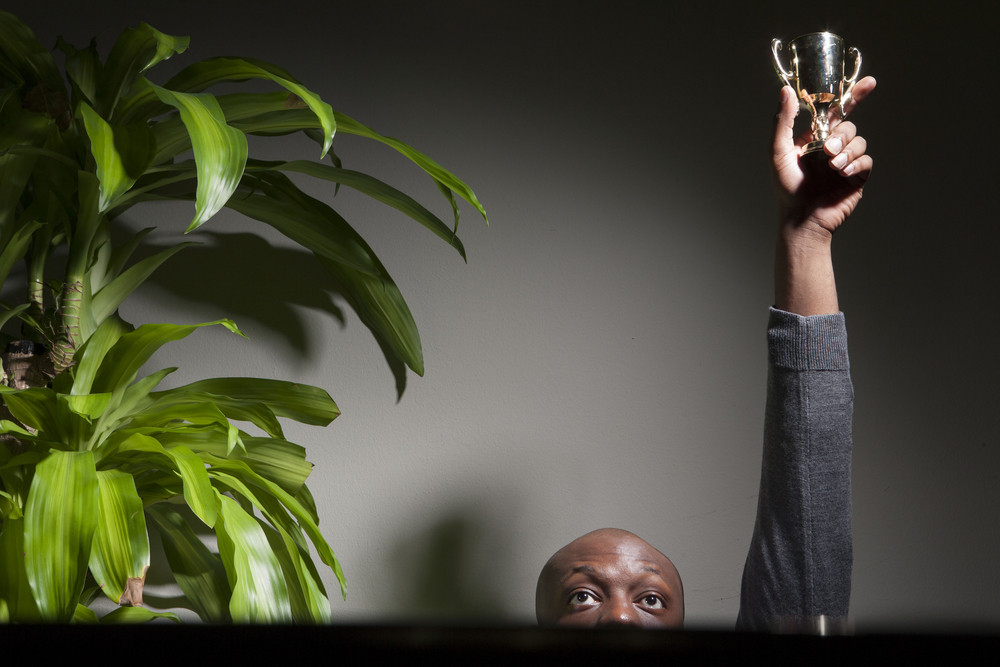 Businessman holding trophy in office