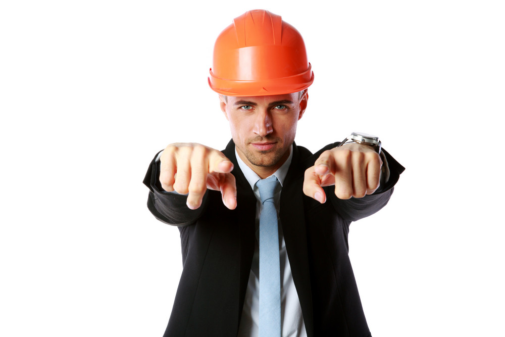 Businessman in hard hat pointing at you over white background
