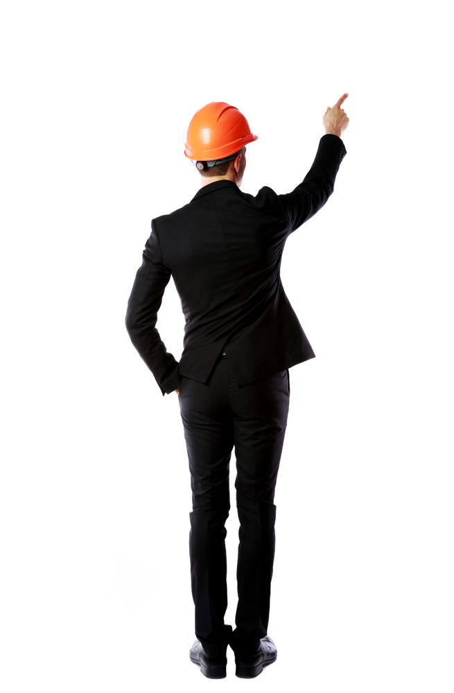 Businessman in helmet points finger up. Isolated on white background