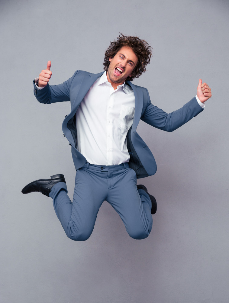 Businessman jumping and showing thumbs up