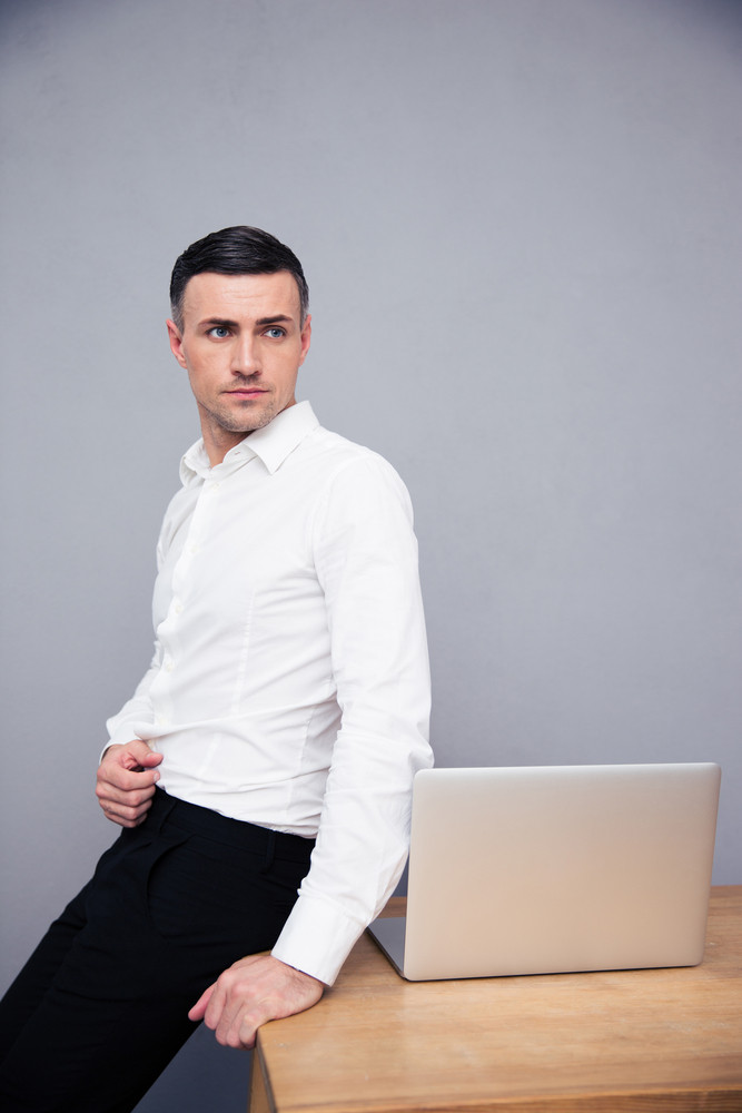 Businessman leaning on the table with laptop and looking away