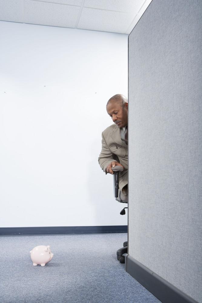 Businessman looking at piggybank