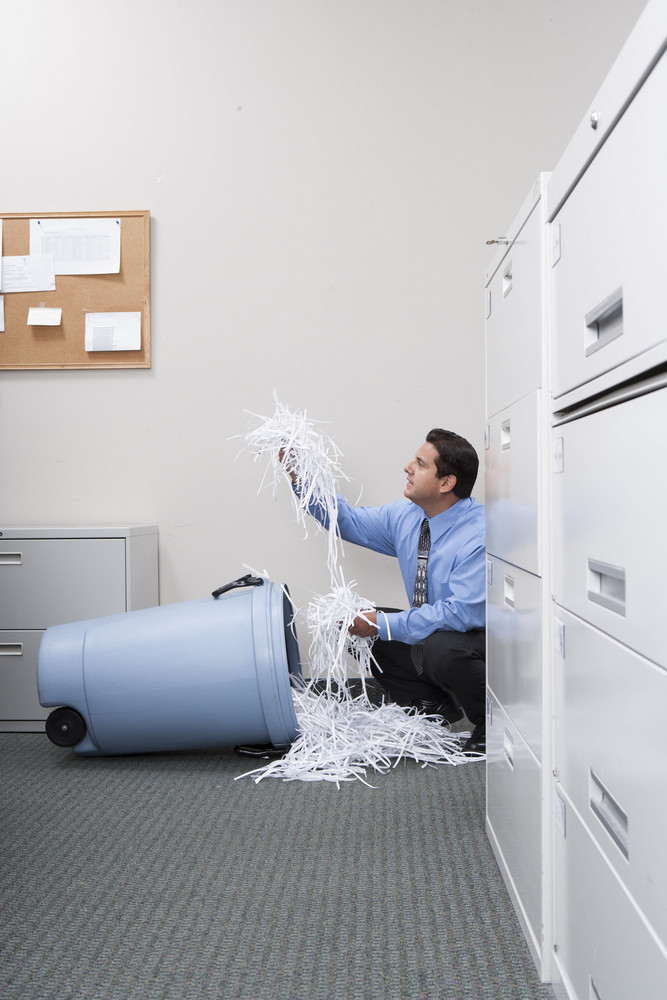 Businessman searching in trash can in office