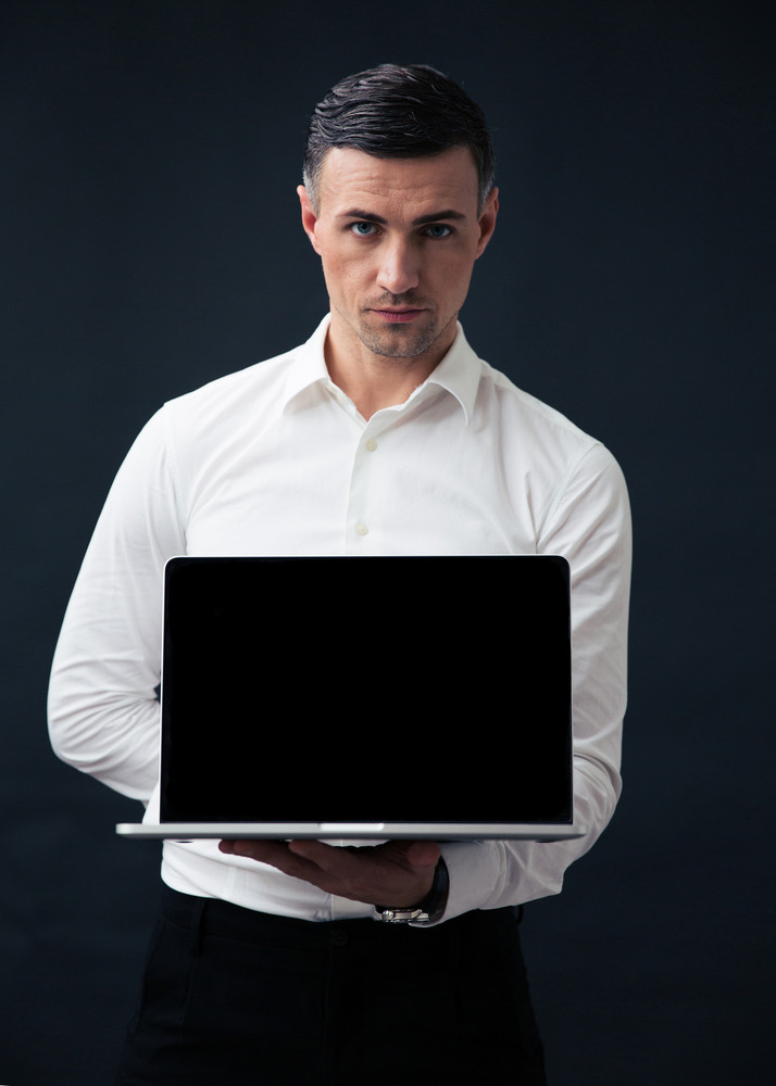 Businessman showing blank laptop screen