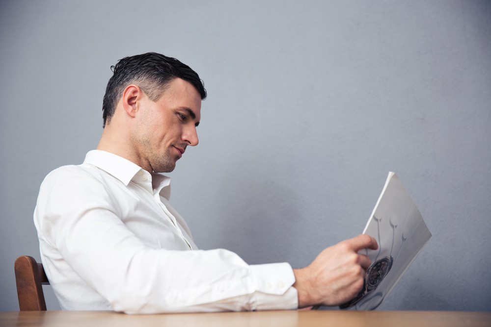 Businessman sitting at the table and reading magazine