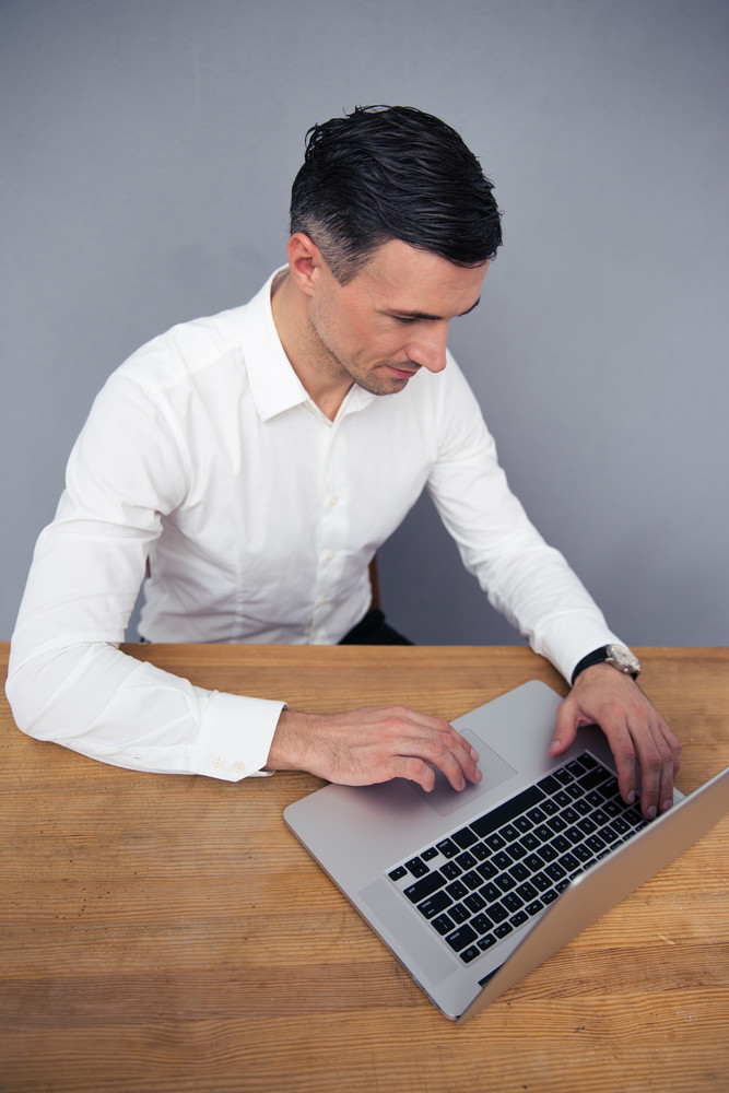 Businessman sitting at the table and using laptop
