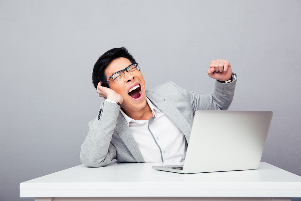 Businessman sitting at the table and yawning