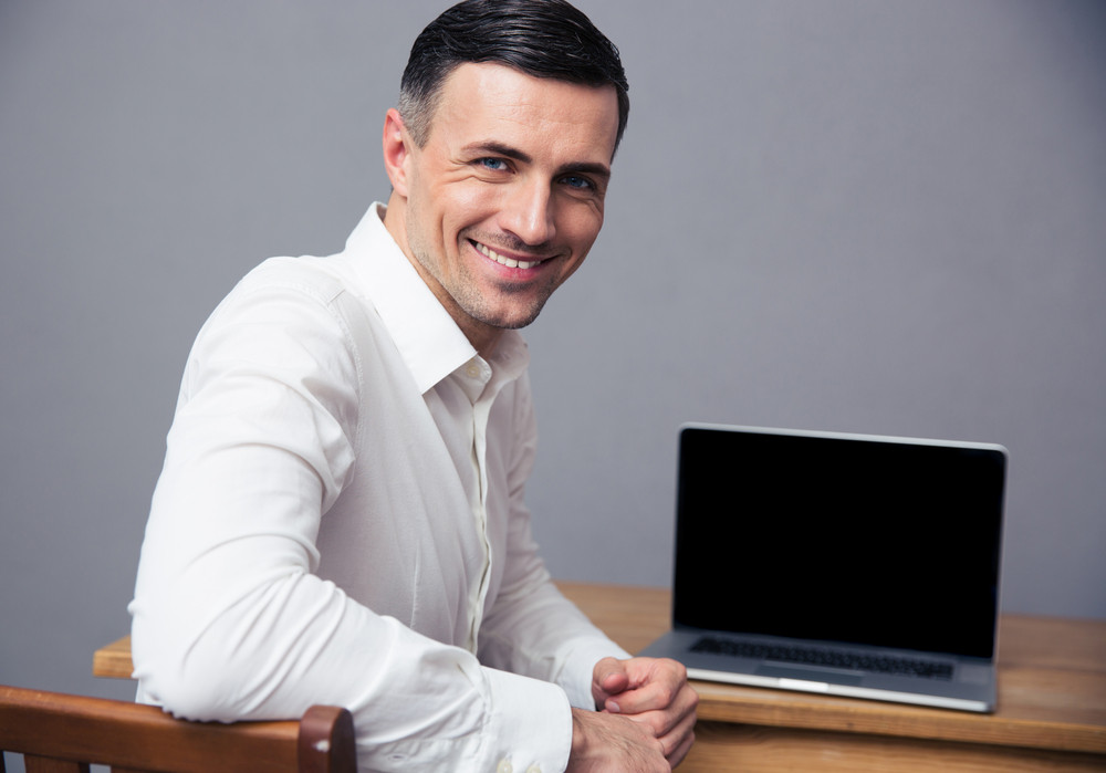 Businessman sitting at the table with blank laptop screen