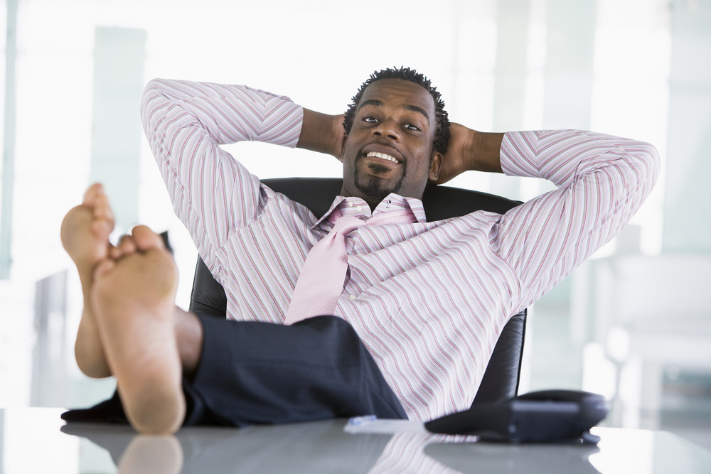 Businessman sitting in office with feet on desk relaxing and smiling