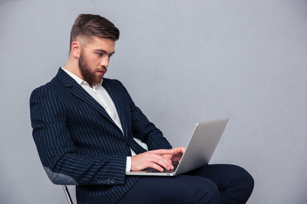 Businessman sitting on office chair and using laptop