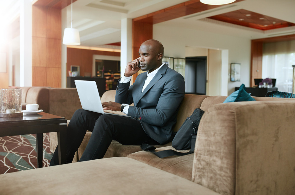 Businessman sitting on sofa with a laptop using mobile phone. Busy african male executive waiting in hotel lobby.