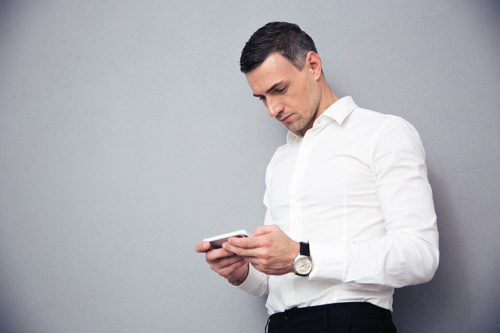 Businessman using smartphone over gray background
