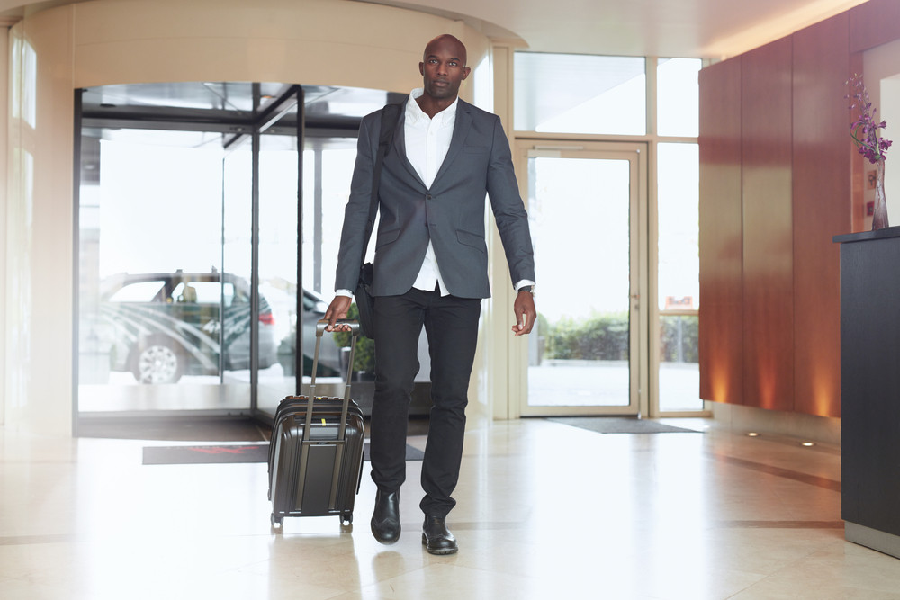 Businessman walking in hotel lobby. Full length portrait of young african executive with a suitcase.