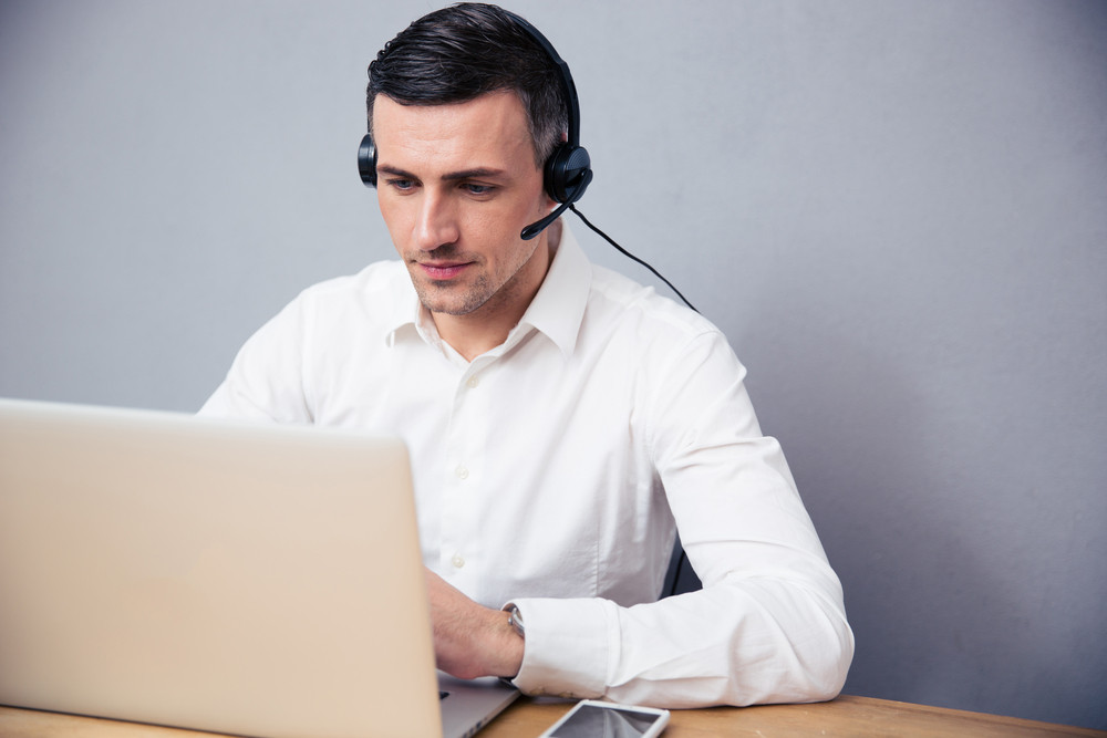 Businessman working on laptop with headphones