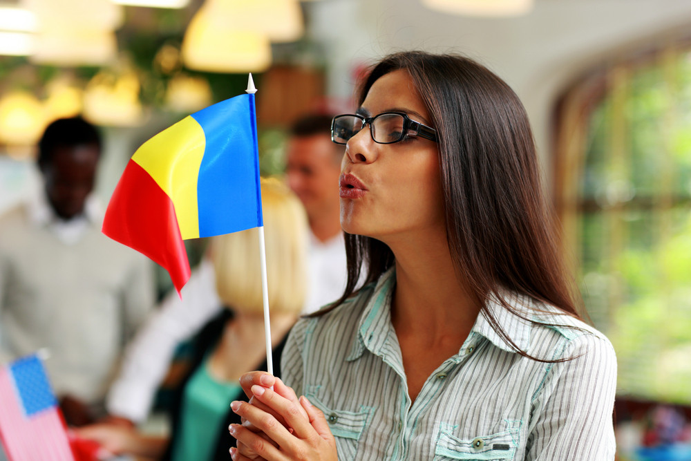 Businesswoman in glasses blowing on flag of Romania