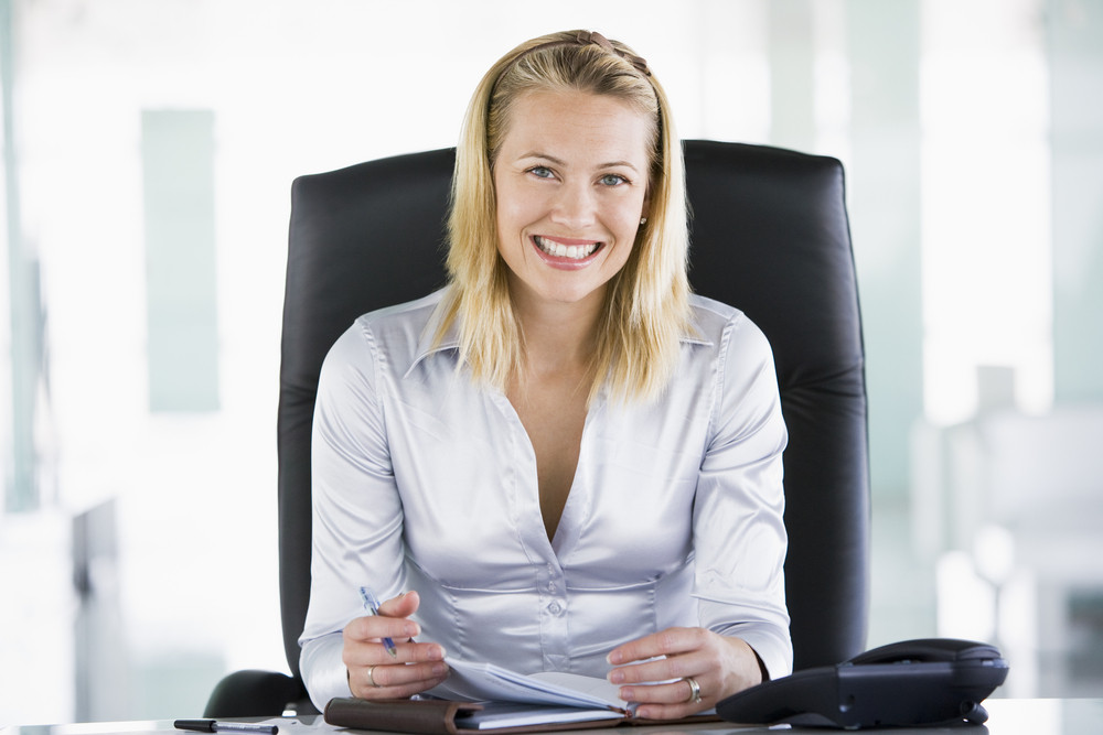 Businesswoman in office with personal organizer smiling