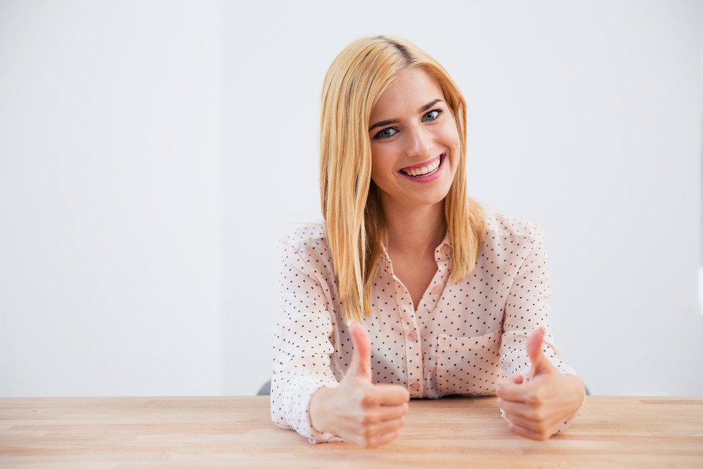 Businesswoman sitting at the table with thumbs up