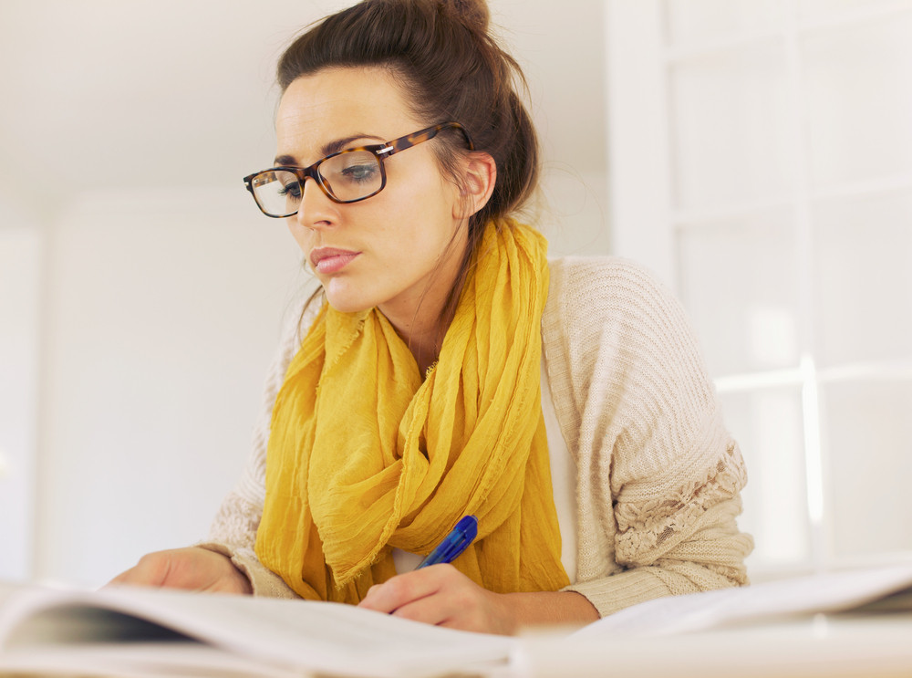 Busy woman reading her textbook and taking down notes