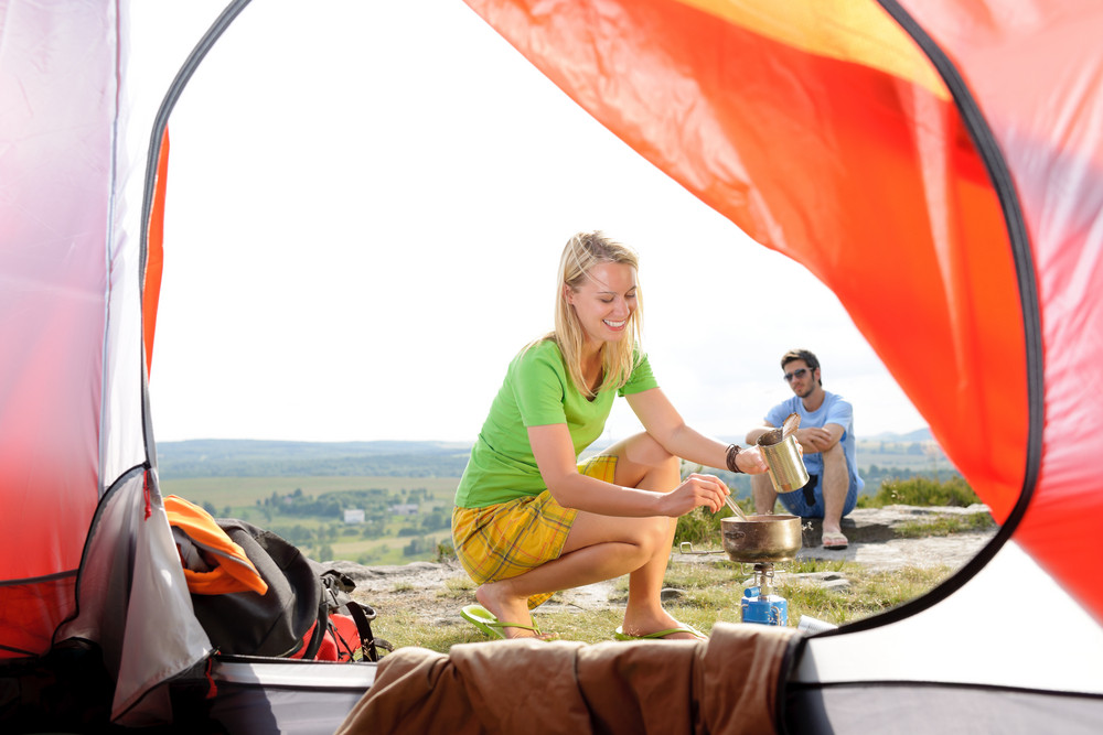 Camping young couple outside tent cook meal countryside view