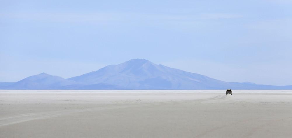 Car traveling a vast desert before a mountain