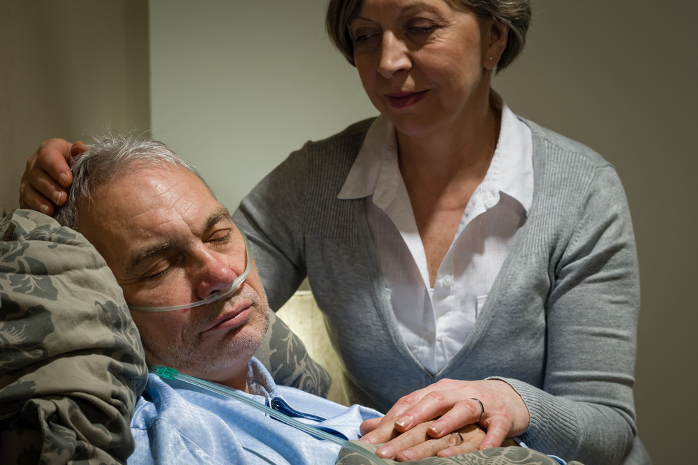 Caring female nurse with sleeping senior male patient