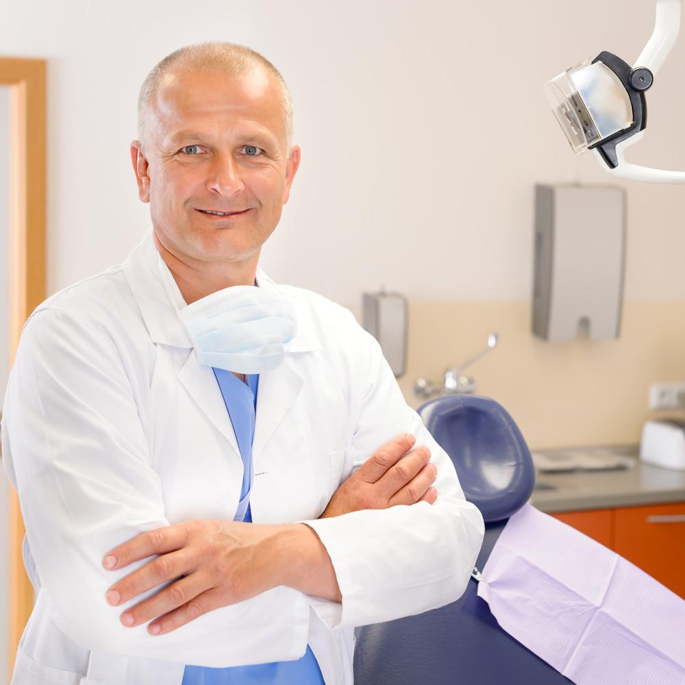 Portrait of mature dentist surgeon posing at office