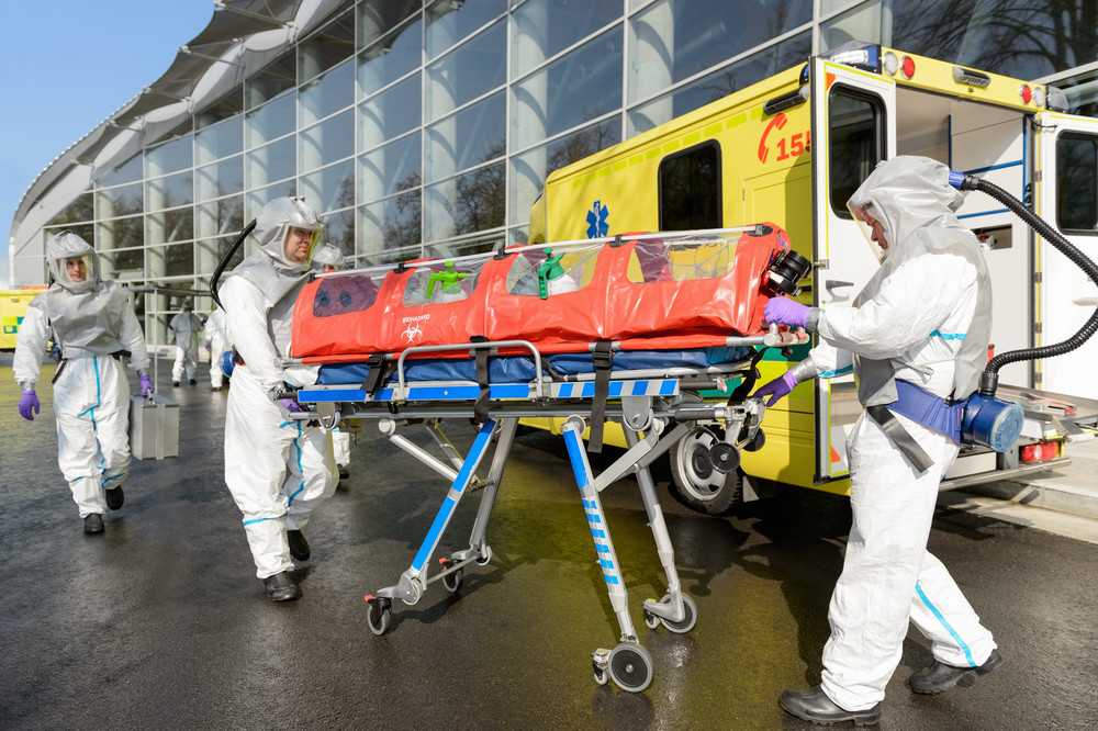 HAZMAT medical team pushing stretcher by ambulance on street