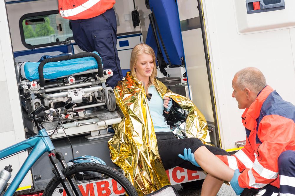 Emergency paramedics with woman bike accident in ambulance help injury