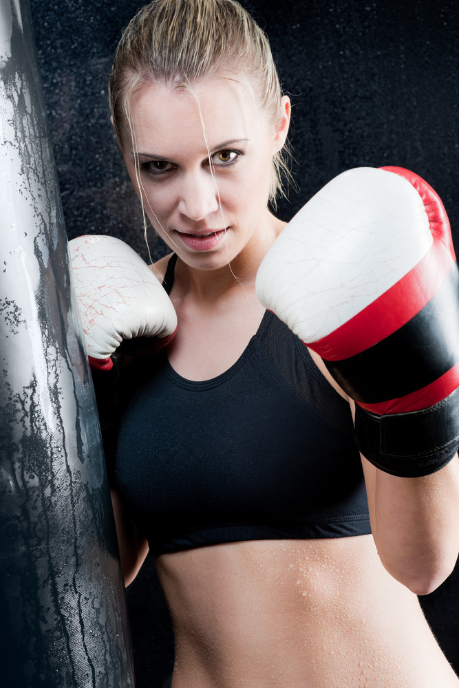 Blond training boxing woman with gloves in gym