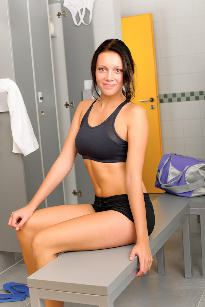 Locker room young sportive woman sitting smiling fitness training