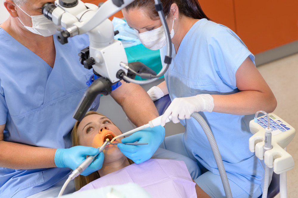 Dentist operating female patient through microscope at surgery office