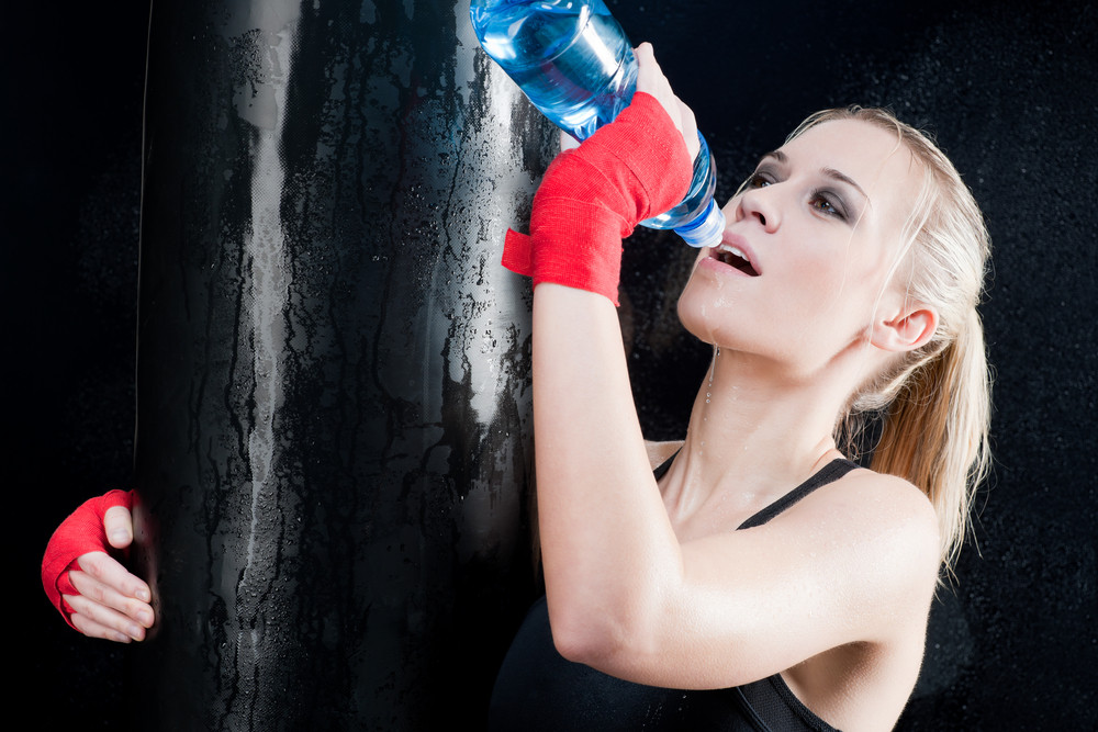 Boxing training woman drink water hold punching bag