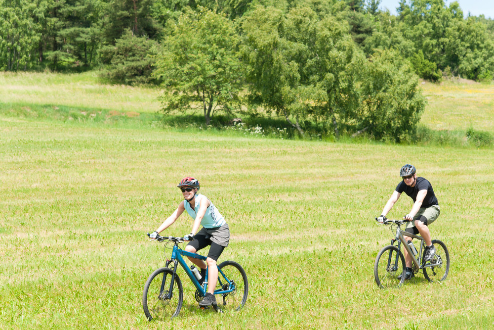 Sport happy couple riding bicycles in coutryside meadows