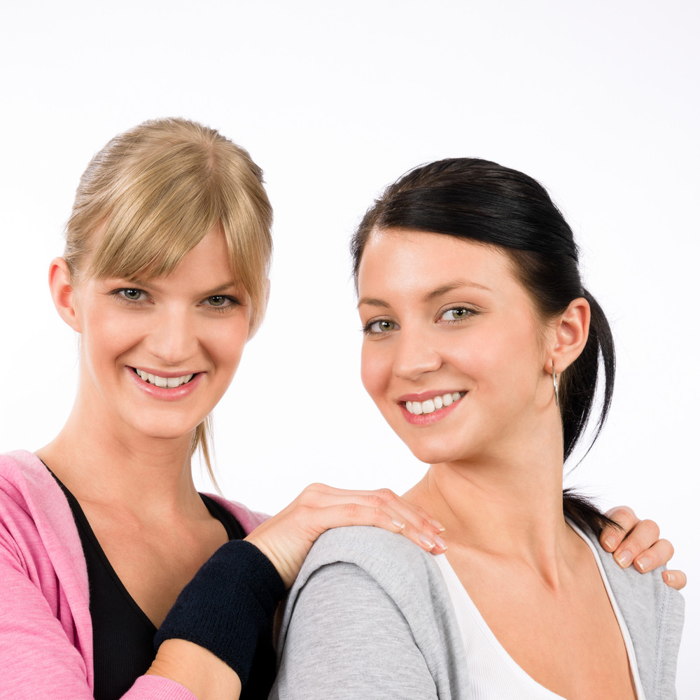 Two women friends sport outfit hugging smiling isolated portrait