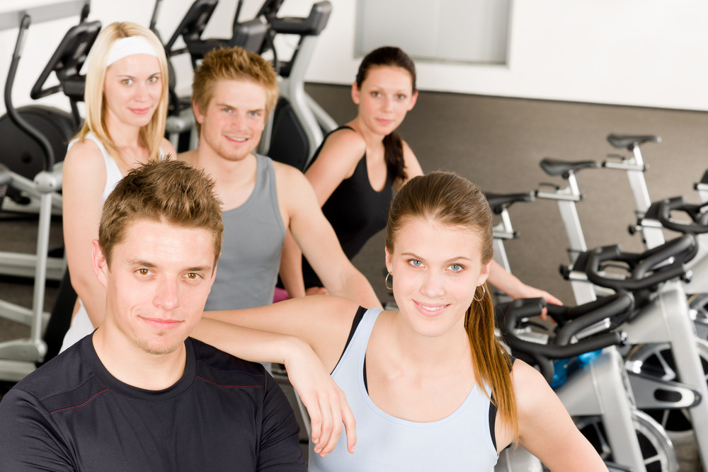 Fitness young group people at gym bicycle portrait