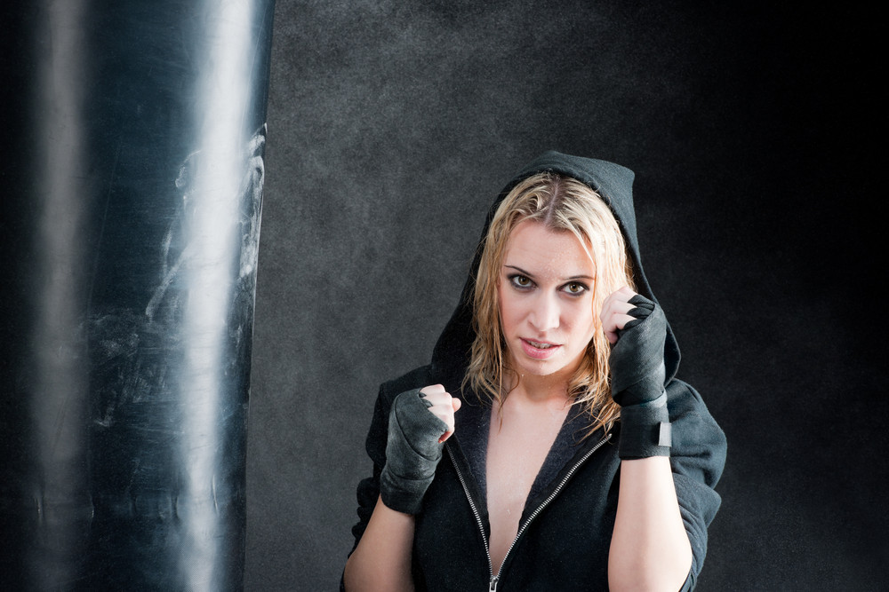 Blond boxing woman in black training with punching bag