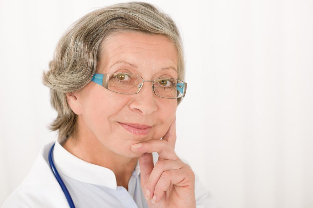 Smiling senior doctor female with stethoscope professional portrait