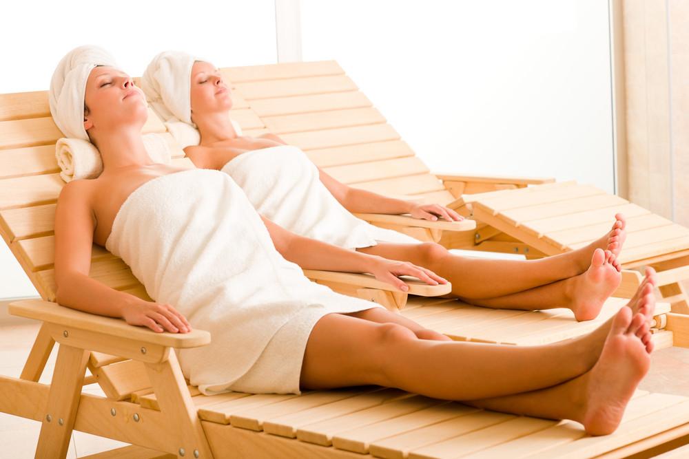 Spa luxury relax room two beautiful women lying on sun-beds