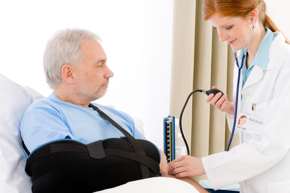 Hospital - doctor check blood pressure of patient with broken arm