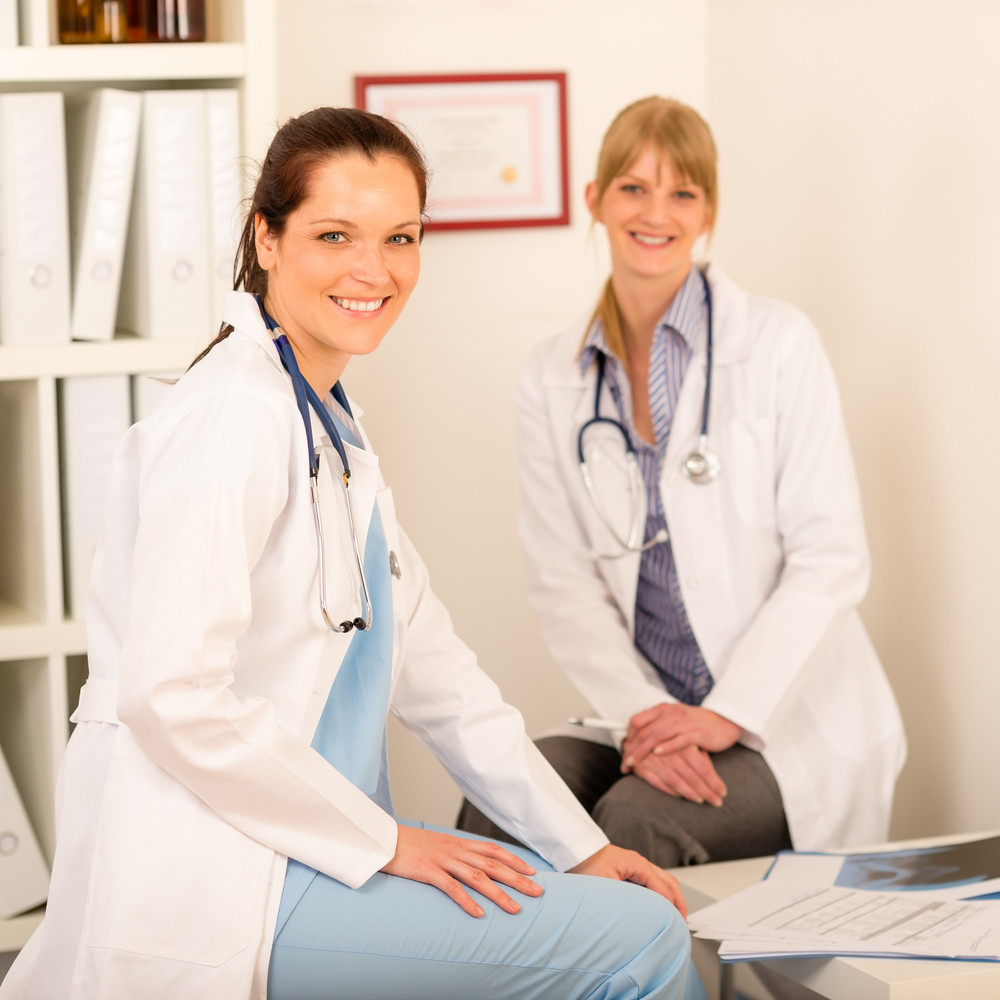 Two female doctors discuss documents at medical office together