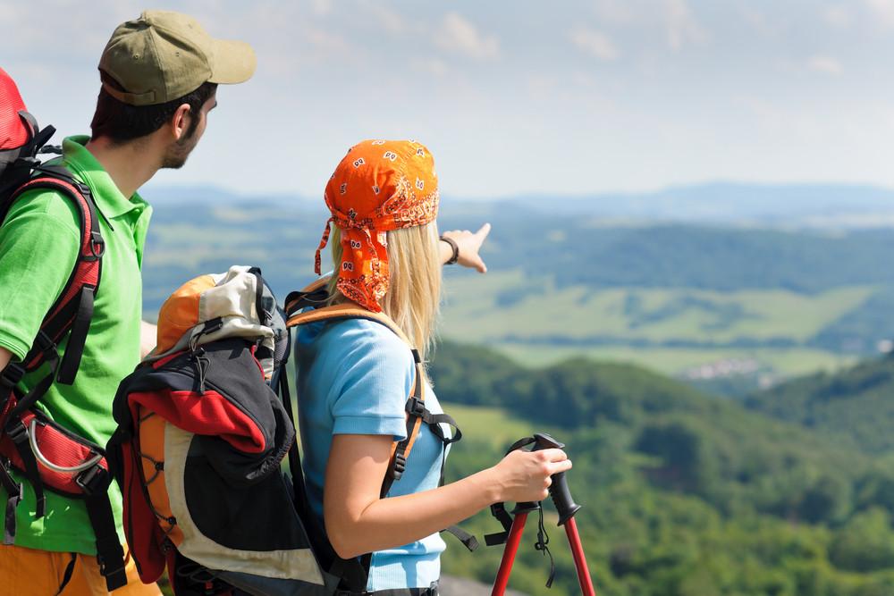年輕夫婦背包遠足兩極美景盡收眼底鄉村